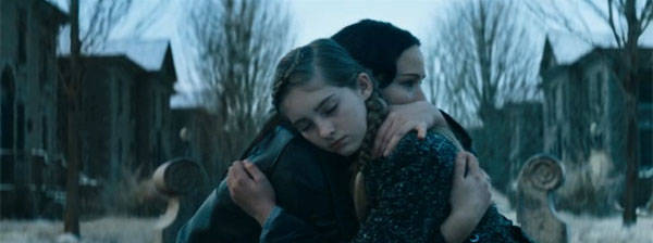 Jennifer Lawrence as Katniss Everdeen and Willow Shields as Primrose Everdeen in Catching Fire