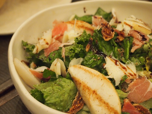 kale and romaine infused salad topped with prosciutto, figs, and walnuts