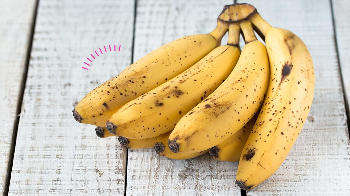 A photo of a bunch of bananas on a wooden table.