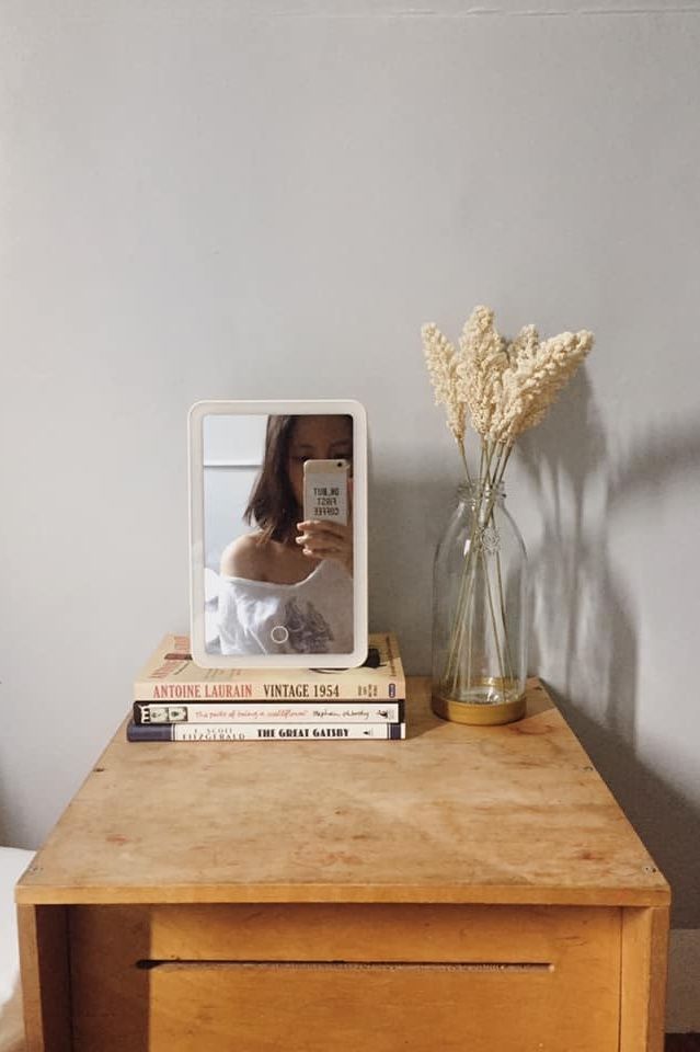 Artificial flowers, mirror, and books on a desk