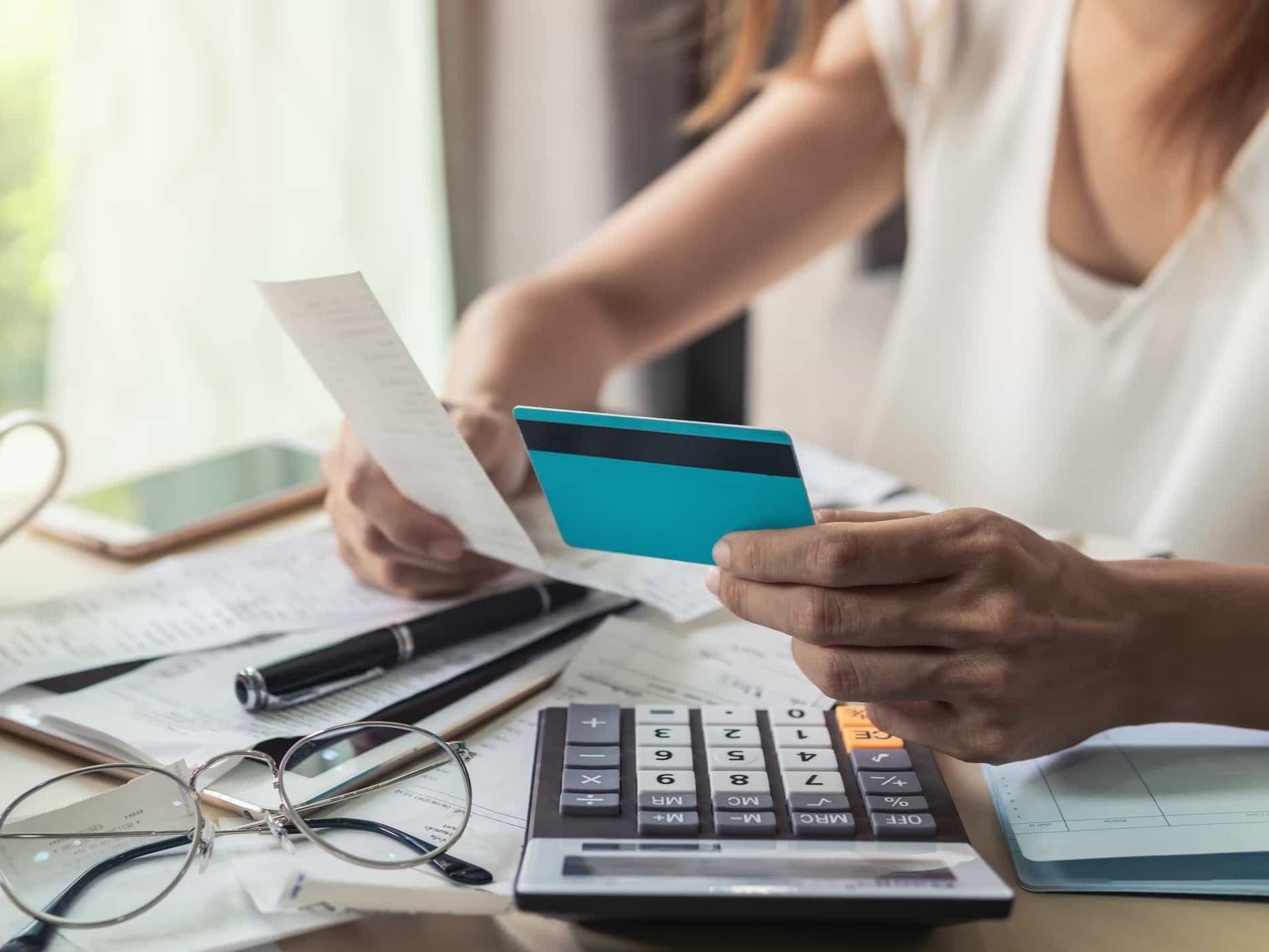 woman holding credit card, computing bills, dealing with money