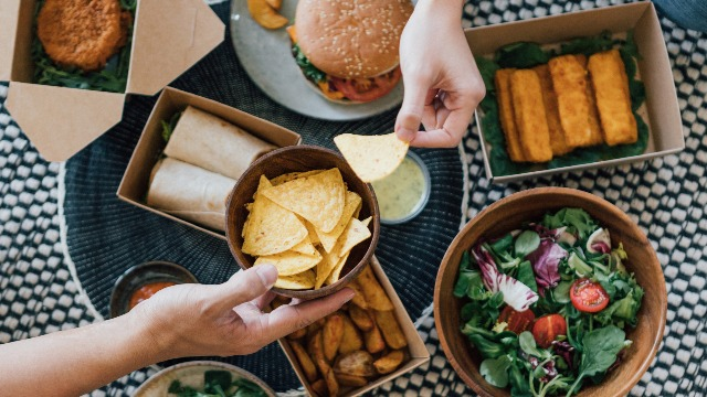 flat lay view of burgers, wraps, salad, and other takeout food