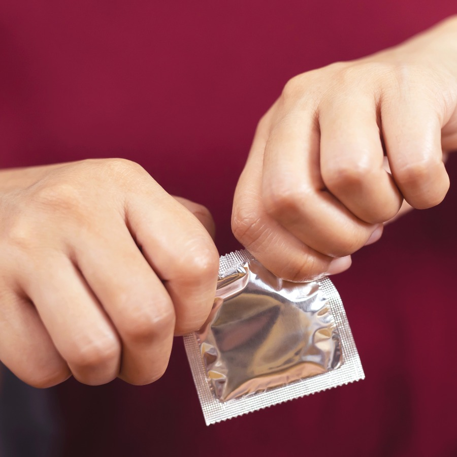 a stock image of two hands opening a condom