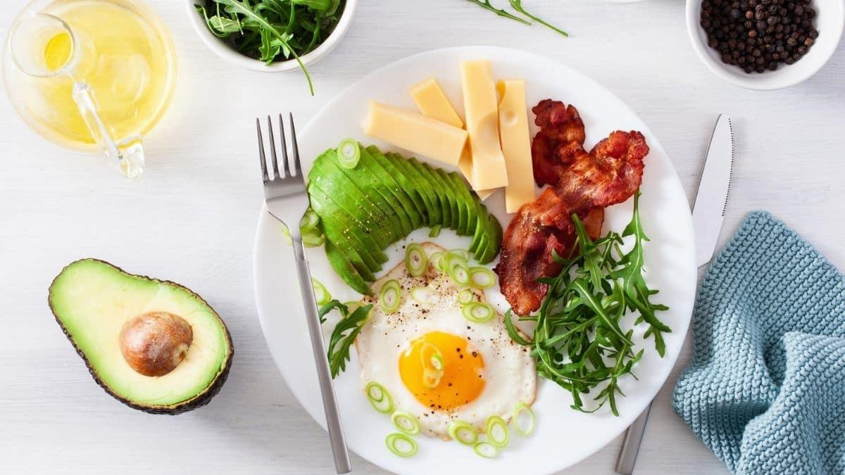 régime pcos: une assiette d'œufs, d'avocats, de fromage, de bacon, de légumes verts, avec de l'avocat et du thé sur le côté