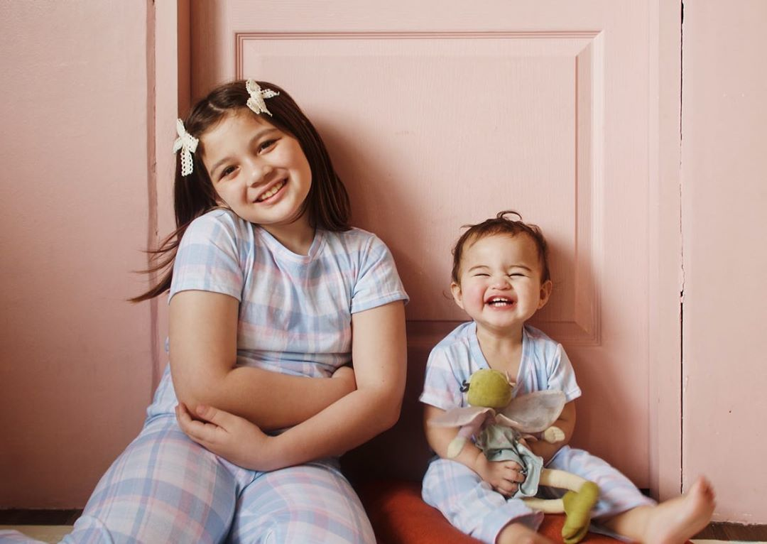 Sisters Ellie Eigenmann and Lilo Eigenmann-Alipayo in matching plaid outfits sitting against a pink wall