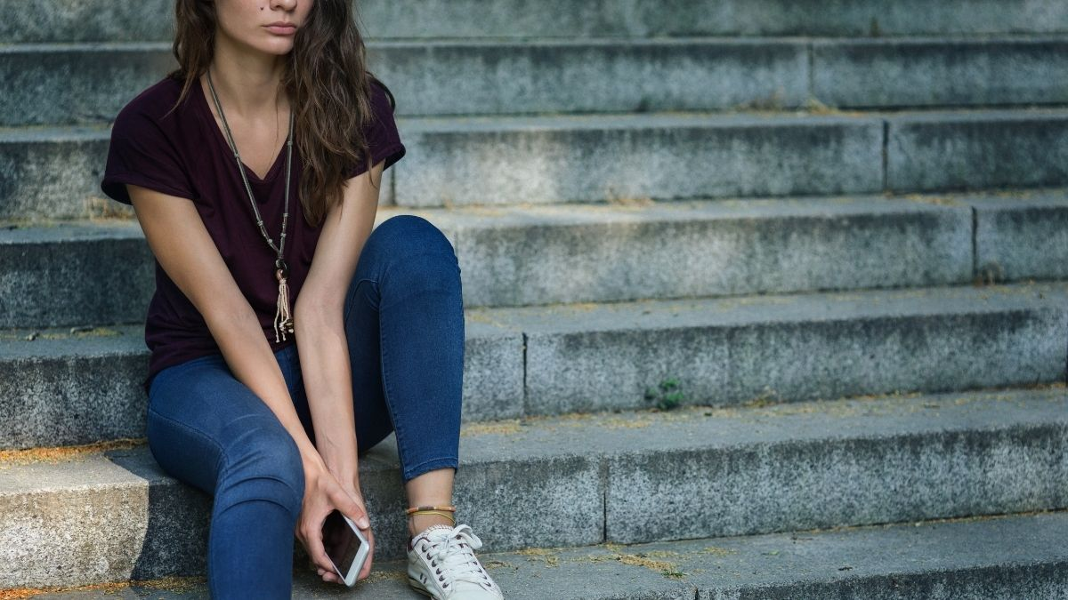 menstruation mood swings: woman thinking while sitting on steps