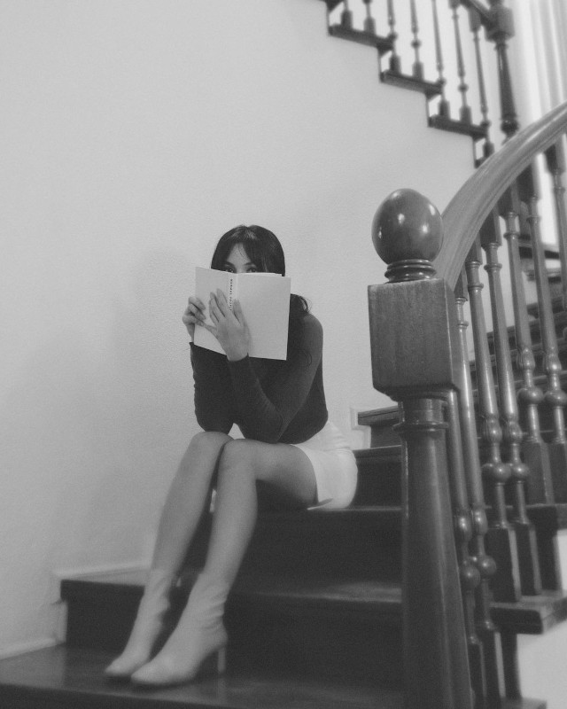 Home Photo Shoot Idea: Sarah Lahbati covering her face with a book.