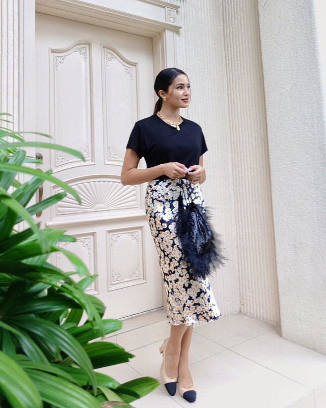 Home Photo Shoot Idea: Sarah Lahbati posing in the doorway wearing a black t-shirt and a floral skirt.