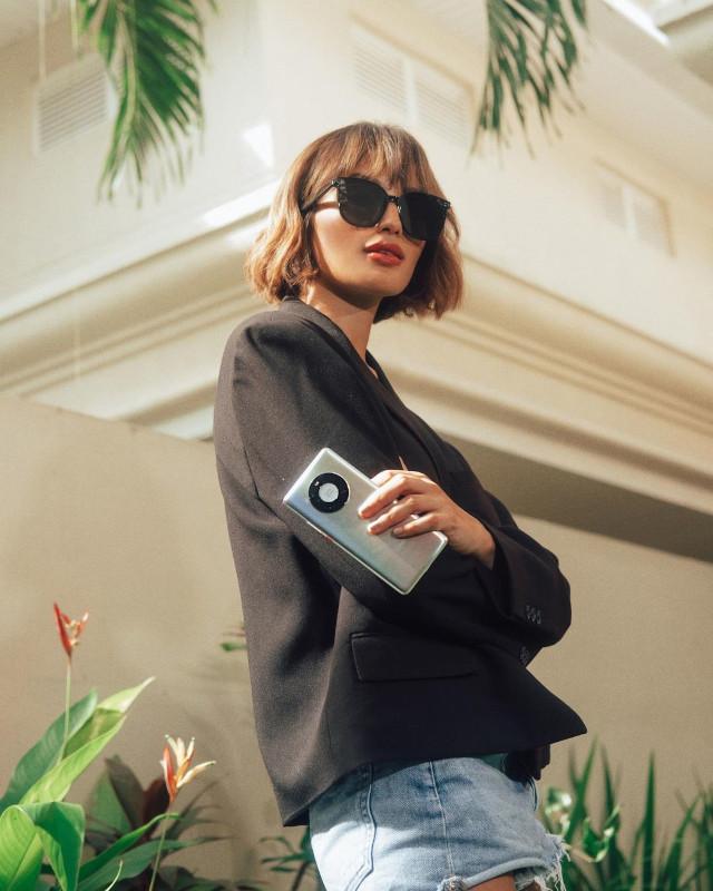 Home Photo Shoot Idea: Sarah Lahbati holding a phone.