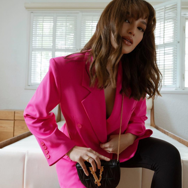 Home Photo Shoot Idea: Sarah Lahbati sitting on the couch, wearing a pink blazer.