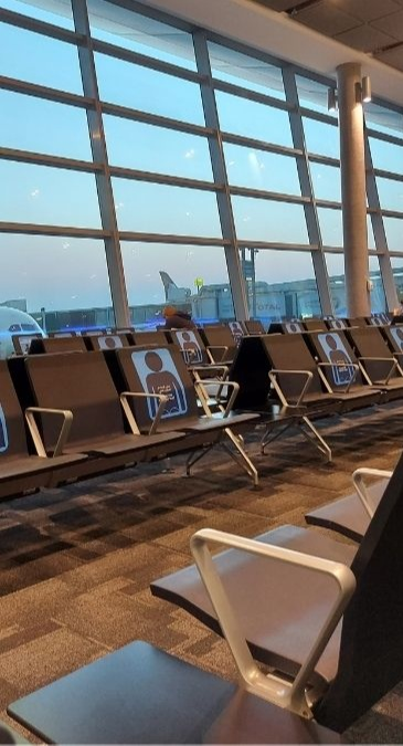 Travel in the new normal: seats at the airport now have social distancing signs on them
