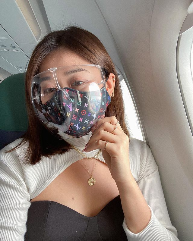 Travel in the new normal: Dianne wearing a face shield inside the airplane