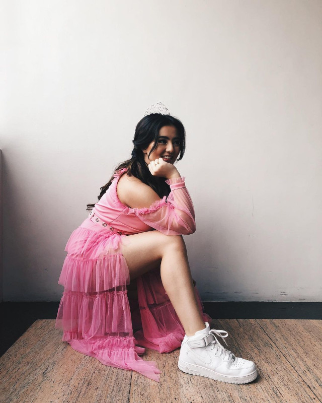 Cassy Legaspi wearing a tiara, pink dress and white sneakers.