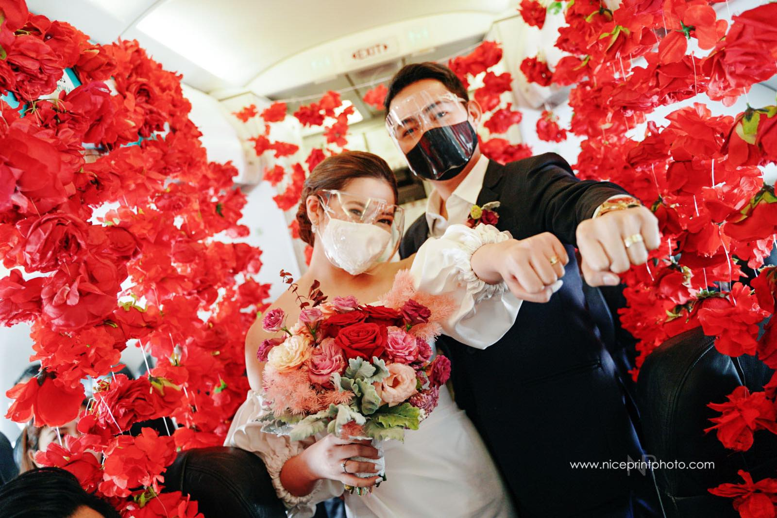 wedding of two flight attendants during a commercial flight: couple showing their rings