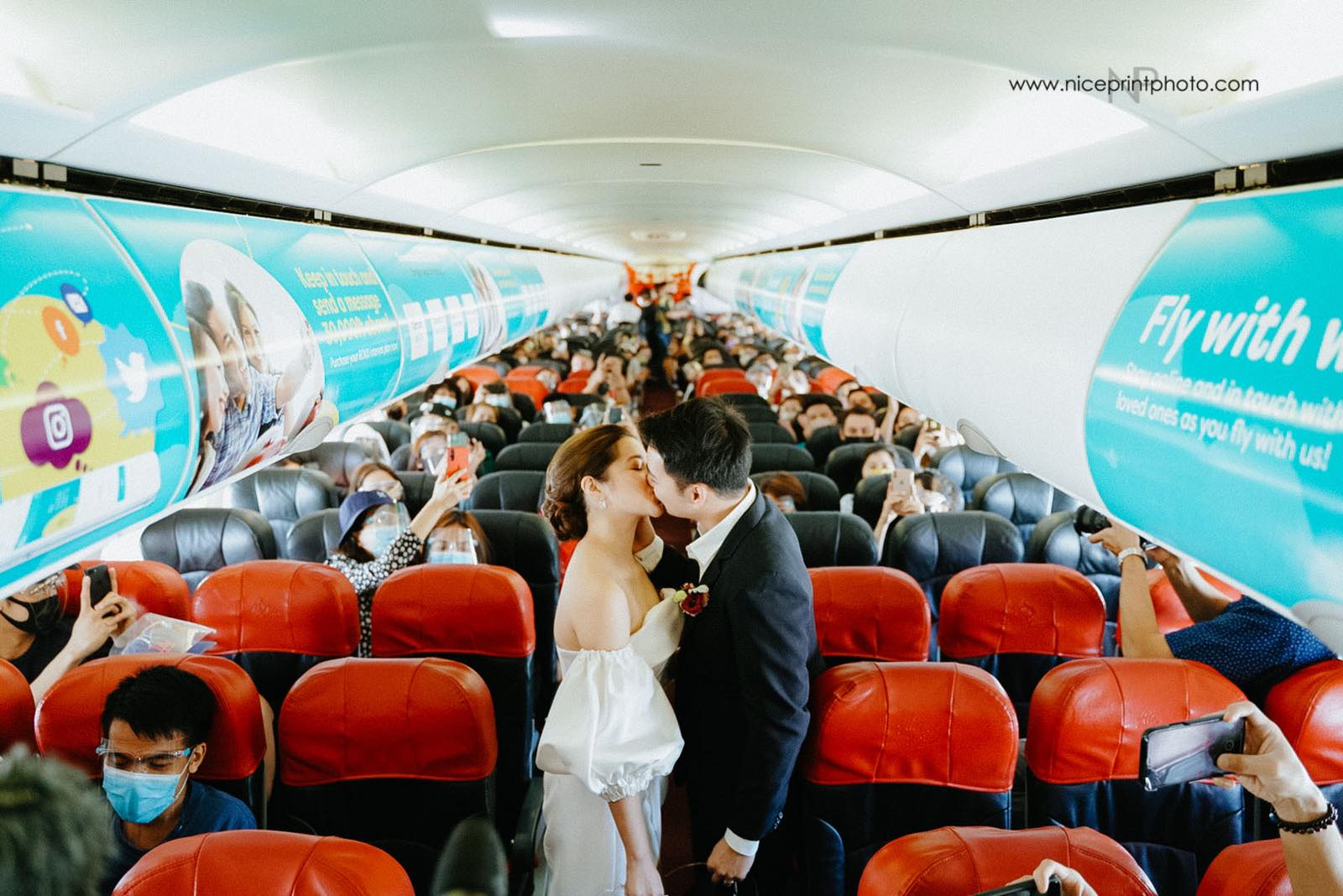 wedding of two flight attendants during a commercial flight: couple kissing