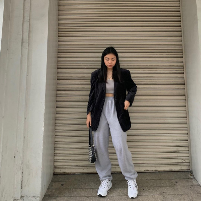 Chelsea Valencia Oversized Blazer Outfit: Black velvet oversized blazer + gray crop top + gray jogger pants + baguette bag + white sneakers