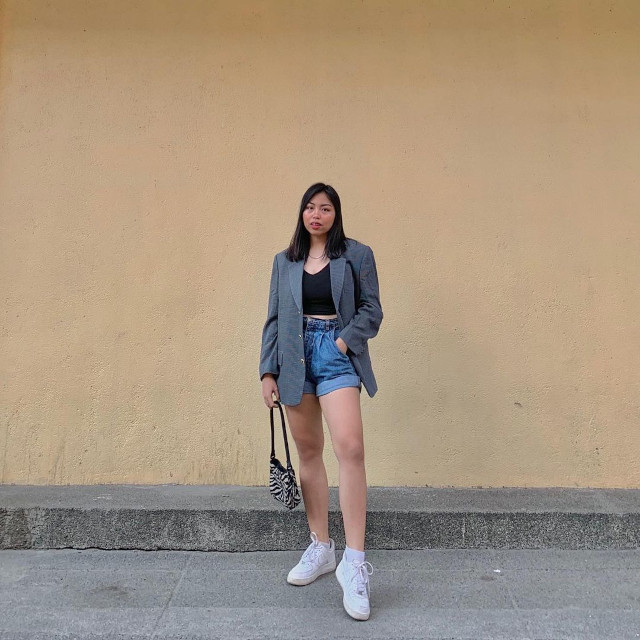 Chelsea Valencia oversized blazer outfit: Gray oversized blazer + black crop top + cuffed denim mom shorts + zebra print baguette bag + white sneakers
