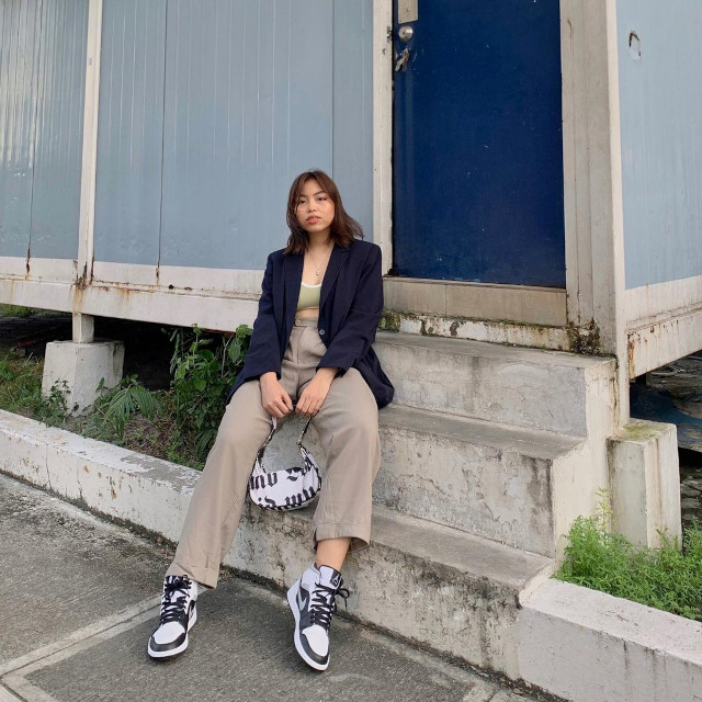 Chelsea Valencia oversized blazer outfit: Navy blue oversized blazer + muted green bralette + high-waist khaki pants + baguette bag + white high top sneakers with black accents