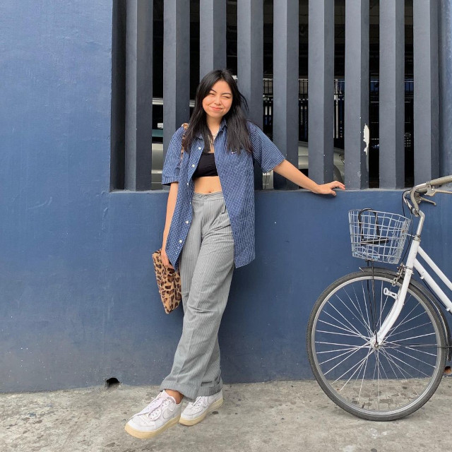 Chelsea Valencia outfit: Oversized blue pinstripe button-down shirt + black bralette + high-waist gray trousers + leopard print bag + white sneakers