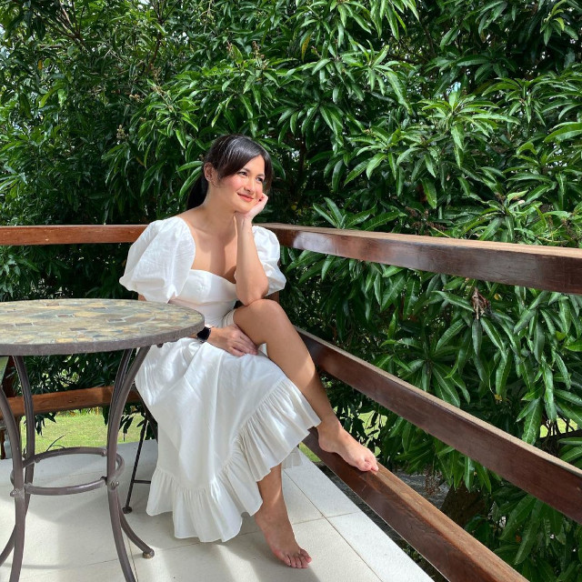 Camille Prats wearing a white dress with puff sleeves