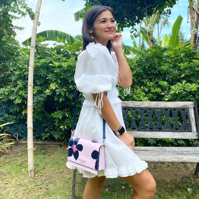 Camille Prats wearing a white dress