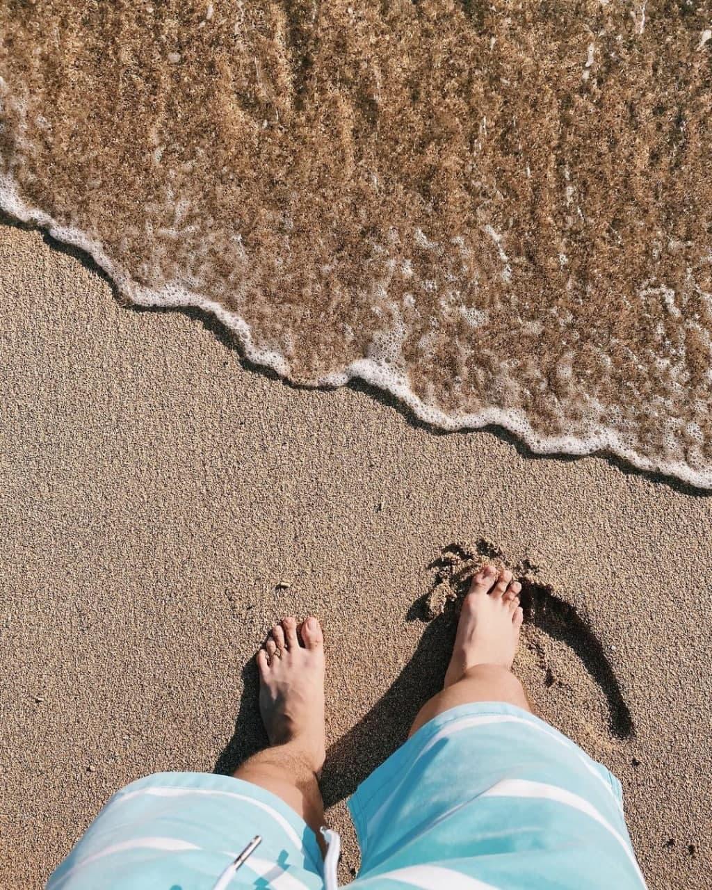 Soft ocean waves featuring a man's feet.