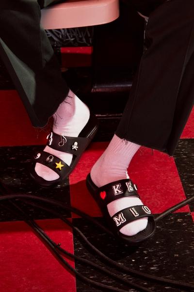 Kemio wearing a pair of black classic Crocs sandals