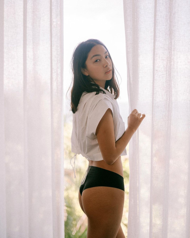 Rei Gernar wearing a white crop top and bikini bottom