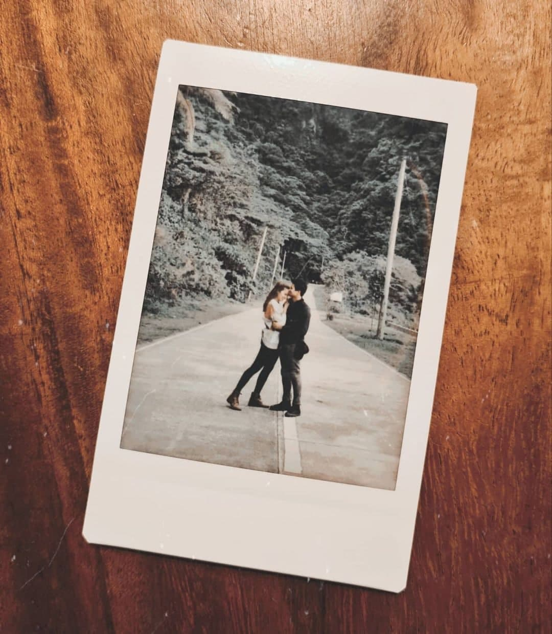 A polaroid photo of Sam Milby and Catriona Gray on a road