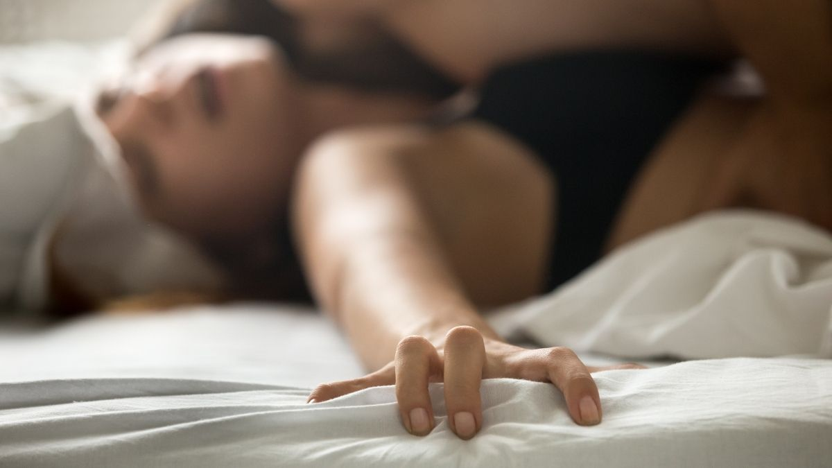 Woman having an orgasm in bed