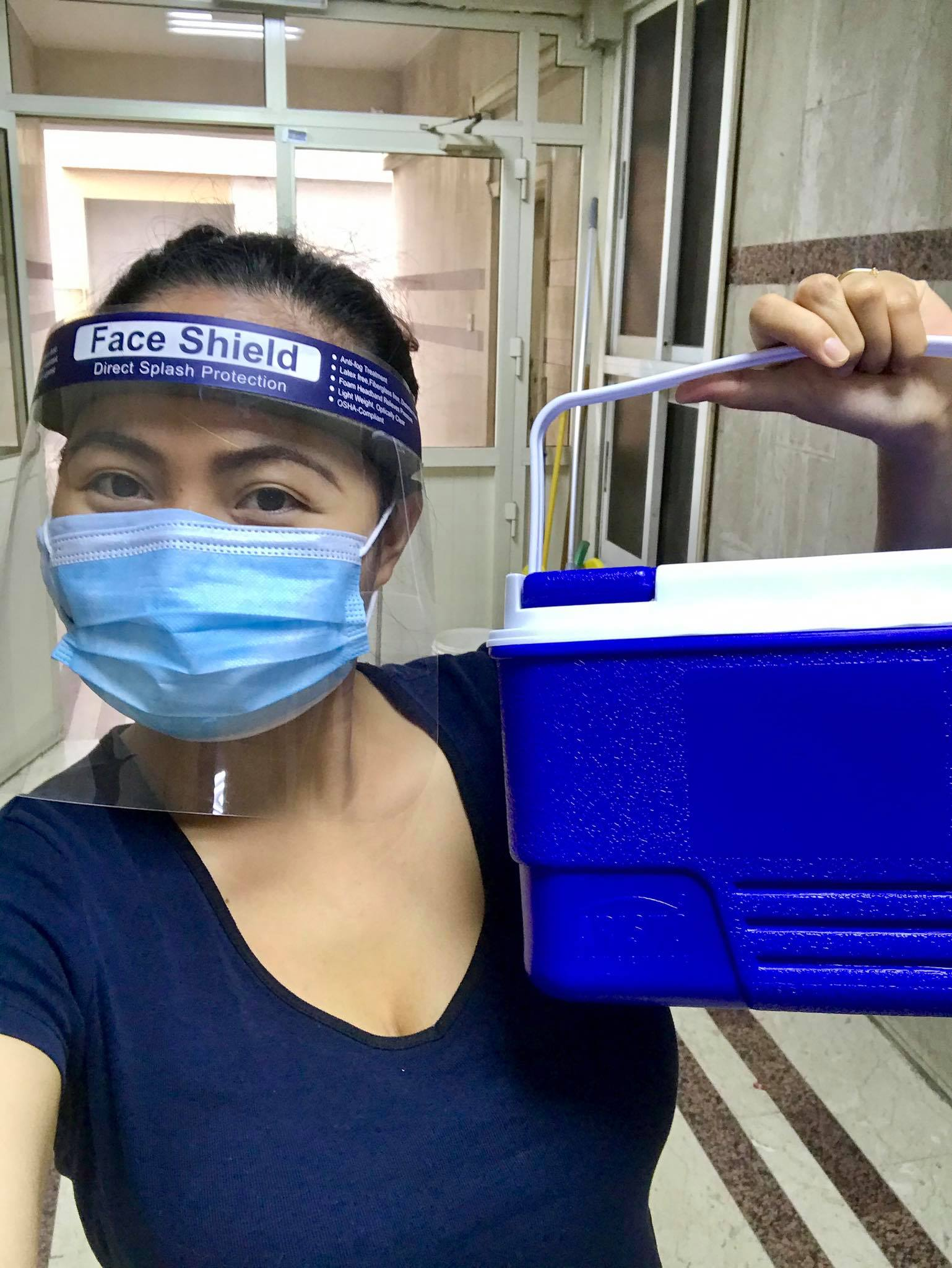 pinay wearing face shield and face mask, holding a cooler with breast milk inside