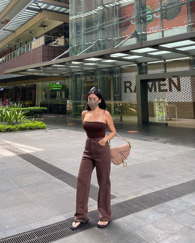 Sexy casual outfit: Spaghetti strap bodysuit + high-waist trousers + chunky thong sandals + saddle bag