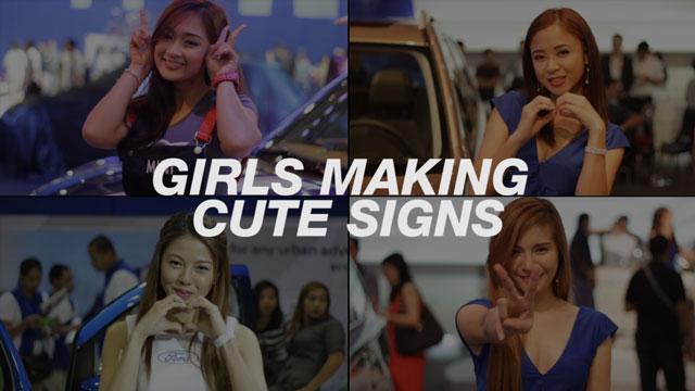 Girls Making Cute Signs At MIAS 2015