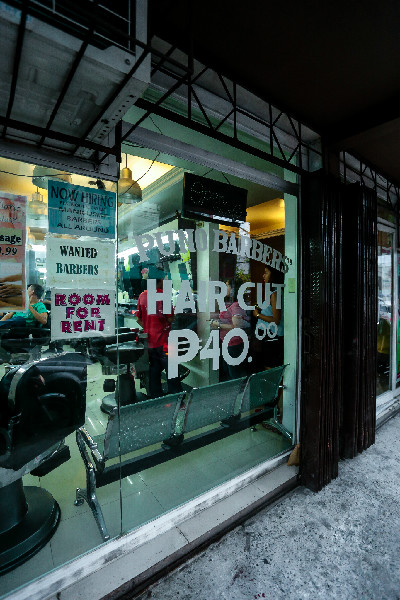 Exterior of the Puno Barbershop with the haircut price and job postings