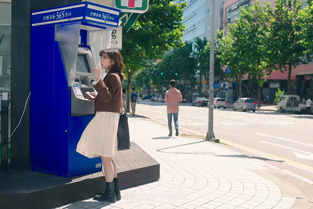 A woman standing by a ATM
