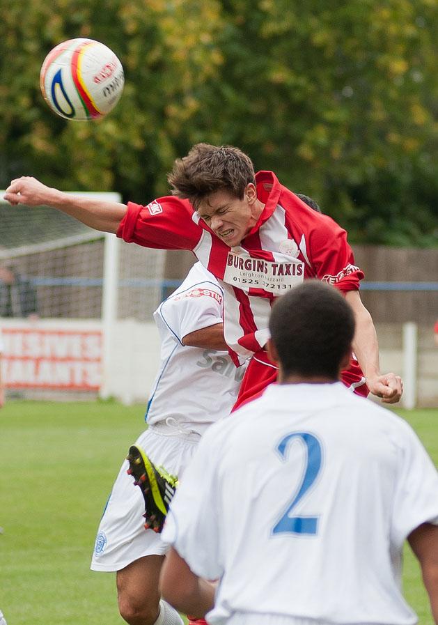 Professional football player heads a ball