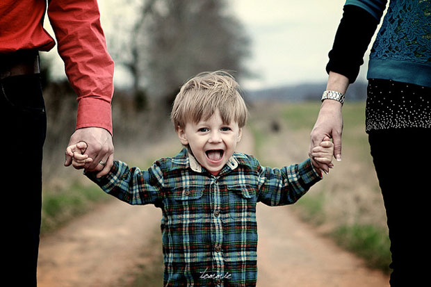 happy child holding mom and dad's hands