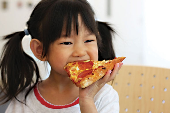 Child eating a pizza slice