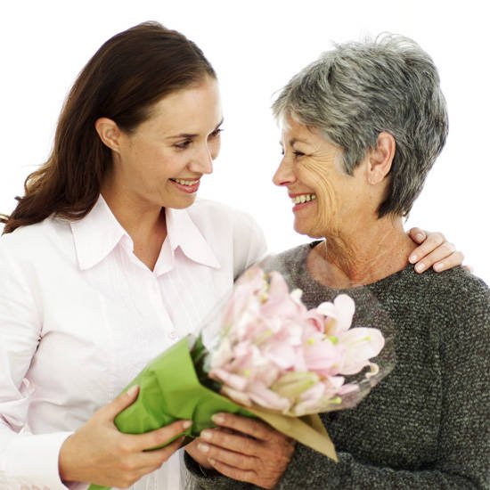 woman gives flowers to mom
