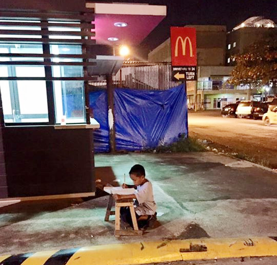 boy studying under streetlamp
