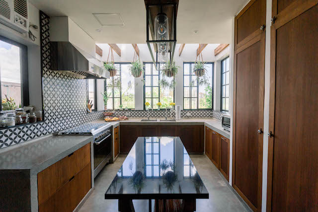 The kitchen island-slash-breakfast nook in the middle has a granite countertop and paired with cast-iron chairs