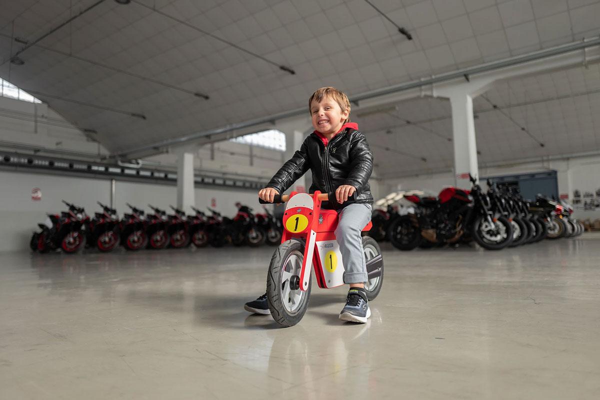 Child riding the MV Agusta Vintage Wooden Balance Bike