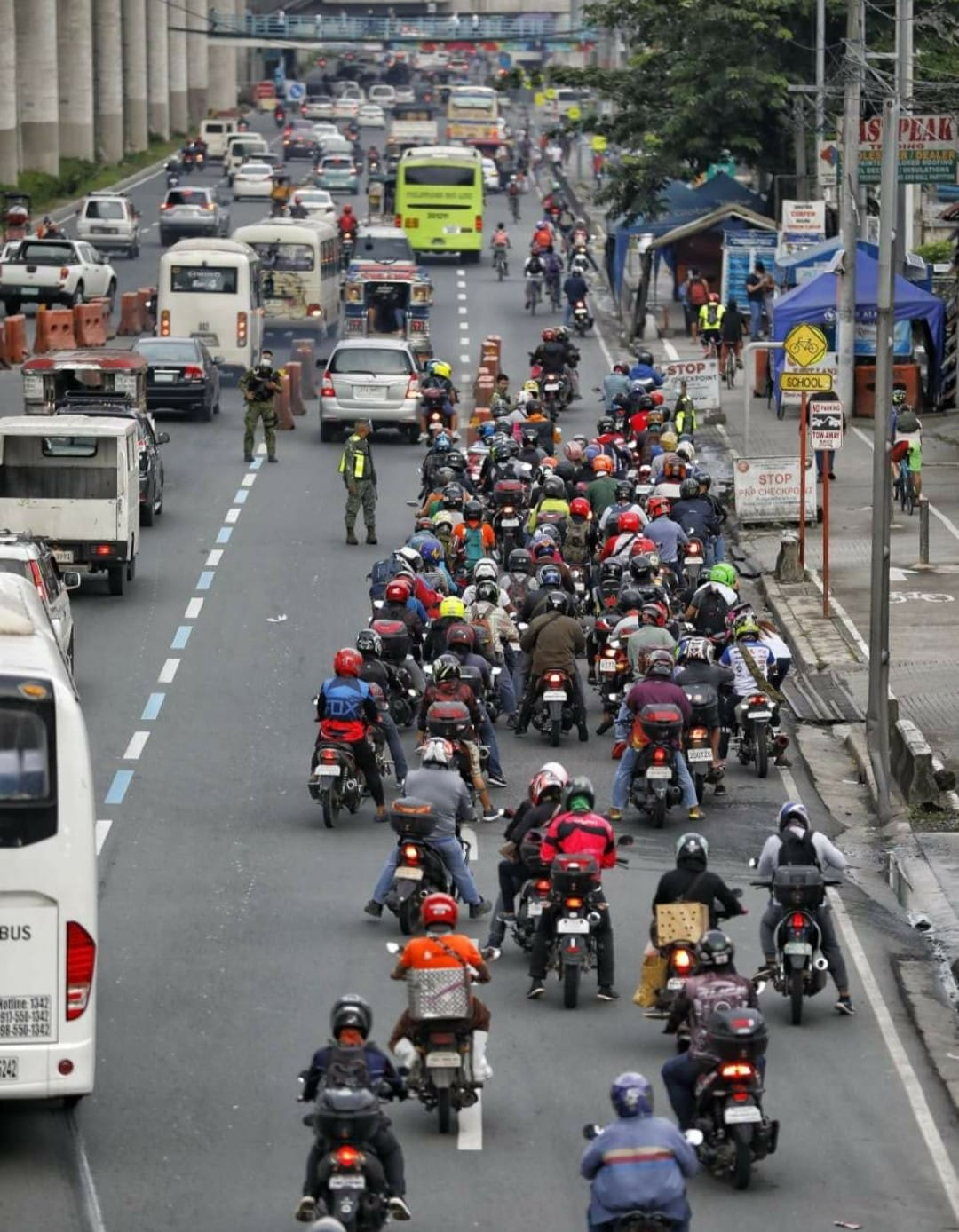 motorcycle riders going through long and crowded lines in passing through the quarantine control points