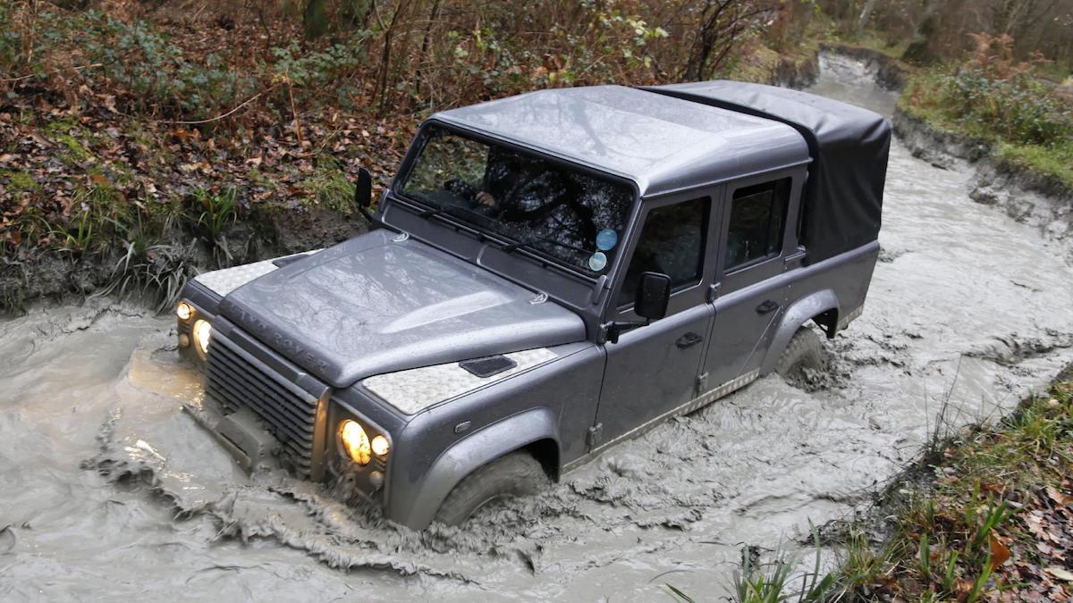 Land Rover Defender half submerged on mud