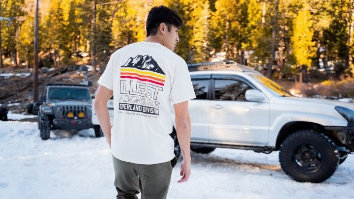 Man wearing a white shirrt with 'illest adventure overland division' print - From the Illest Overland Adventure