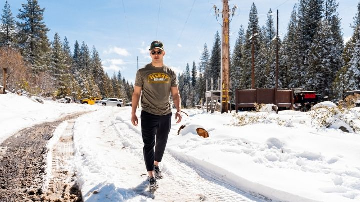 Man walking on snow wearing an olive shirt - From the Illest Overland Adventure
