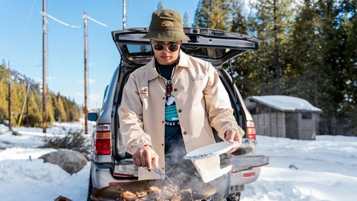 Man cooking BBQ with a cream jacket - From the Illest Overland Adventure