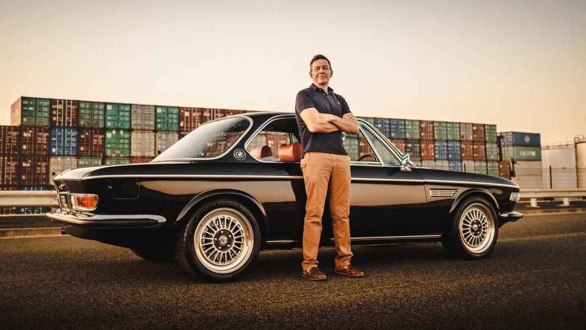 John Ward from Fuel Bespoke Designs poses beside a restomod BMW 2800 CS