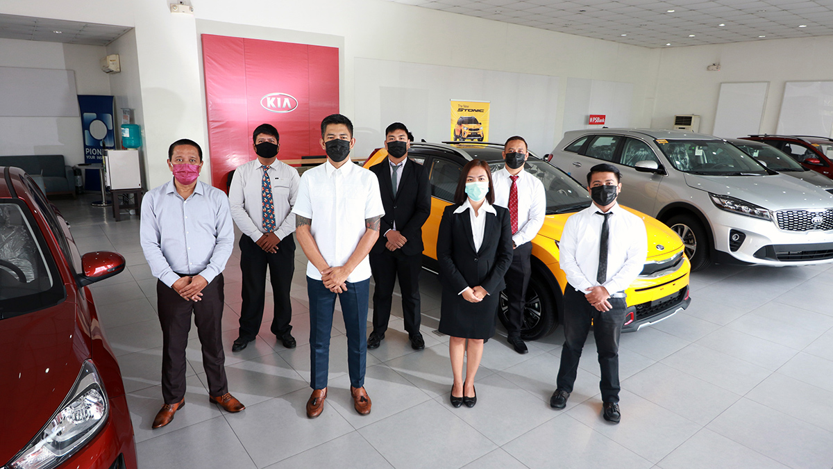 Employees of the newly-opened Kia Cainta dealership pose in their showroom