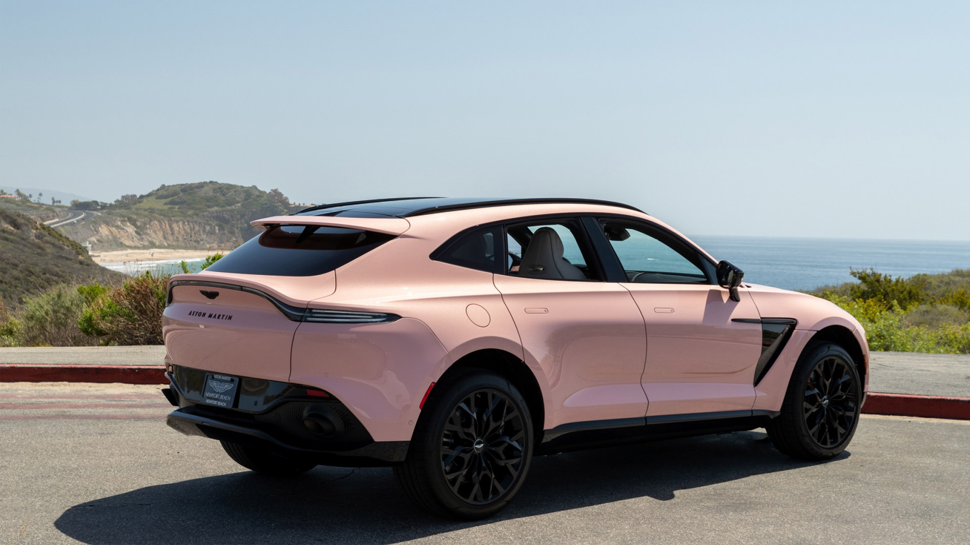 The Aston Martin DBX in Vibrant Coral Angled Rear View